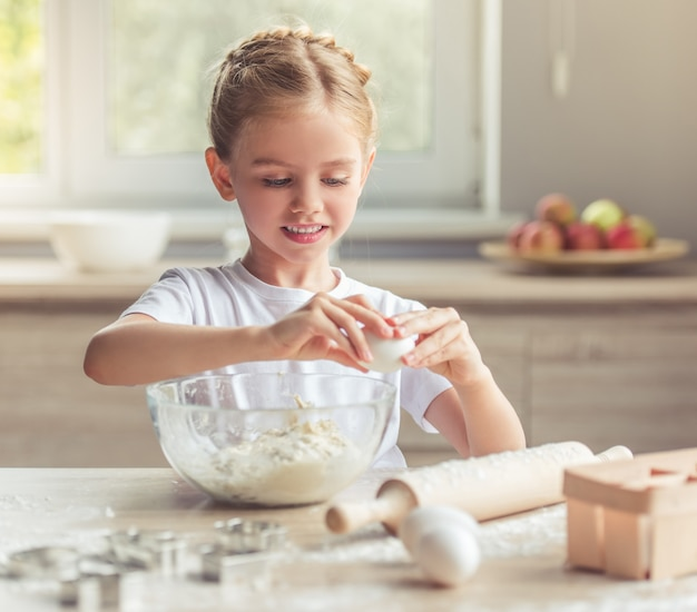 Smiling while kneading the dough for baking in the kitchen