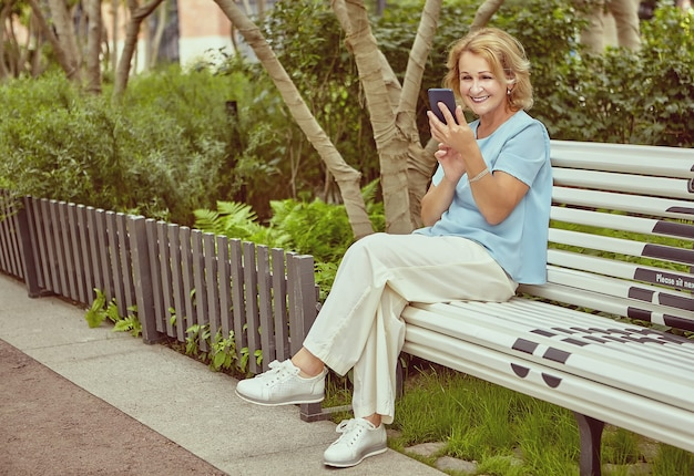 Smiling white attractive aged lady about 62 years old is sitting on bench with social distancing markup in public park.