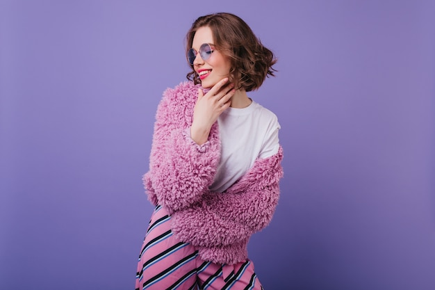 Smiling white girl with short haircut posing on purple wall. graceful european lady in bright fluffy jacket.