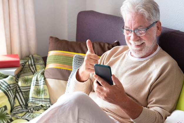 Smiling white-haired senior man in lockdown at home video calling with family with his smart phone. bright light from the window. old retired people using wireless technology