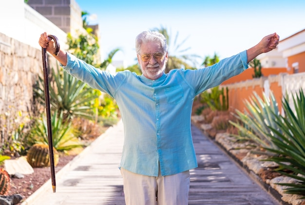 杖を持って屋外で笑顔の白髪の年配の男性。