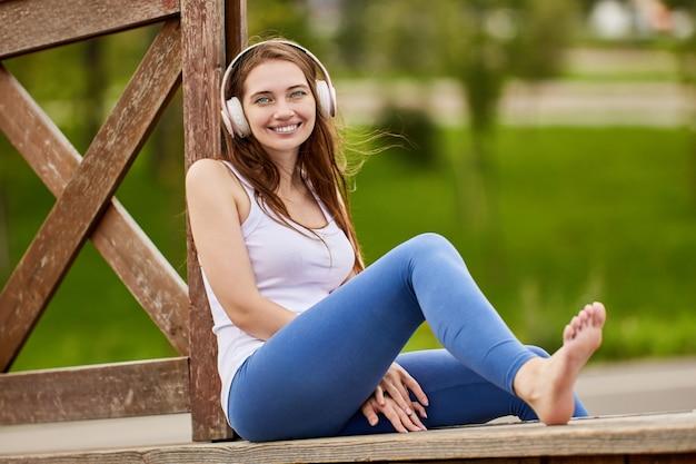 Улыбающаяся белая женщина в наушниках сидит в парке летом