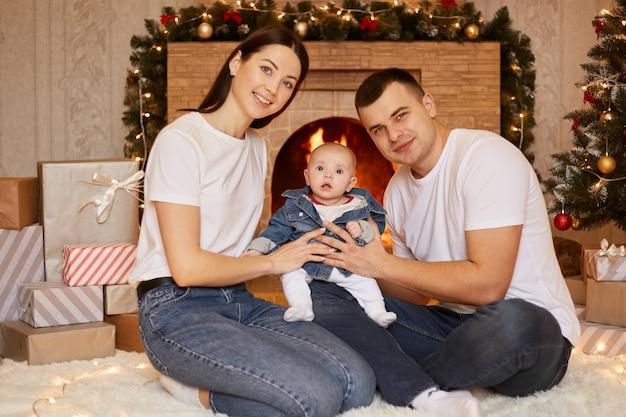 幸せな顔の表情でカメラを見ながら、クリスマスツリーと暖炉を背景に自宅の床に座っている小さなよちよち娘と笑顔の妻と夫。