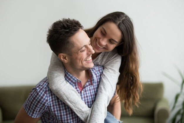 Smiling wife laughing embracing young husband piggybacking her at home