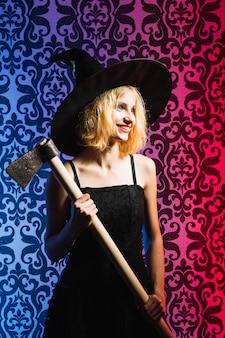 Smiling witch girl with axe
