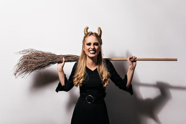 白い壁に立っている怖い化粧と笑顔の魔女。悪の笑いでポーズをとっている魅力的な吸血鬼の屋内写真。