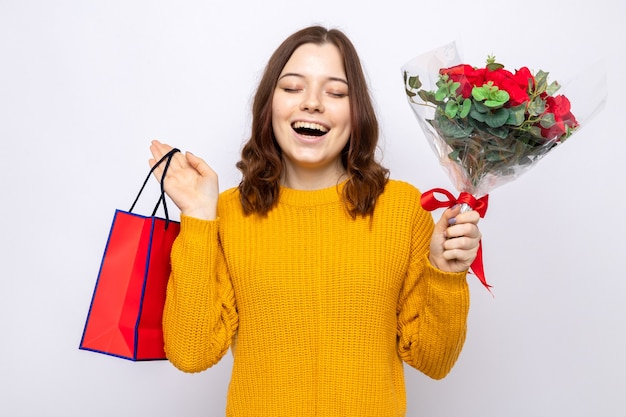 Smiling with closed eyes beautiful young girl on happy woman's day holding gift bag with bouquet isolated on white wall