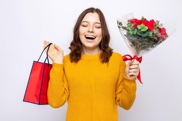 흰 벽에 꽃다발이 든 선물 가방을 들고 행복한 여성의 날 아름다운 어린 소녀가 눈을 감고 웃고 있다