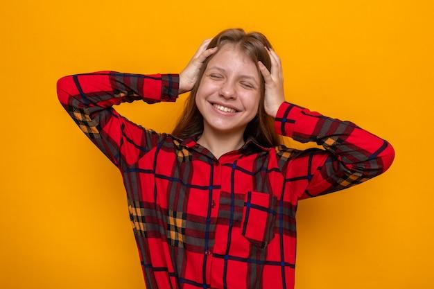 目を閉じて笑って頭をつかんだ赤いシャツを着た美しい少女
