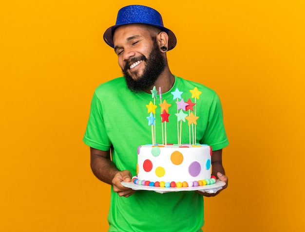 目を閉じて笑顔の若いアフリカ系アメリカ人の男がケーキを持ってパーティーハットをかぶっています