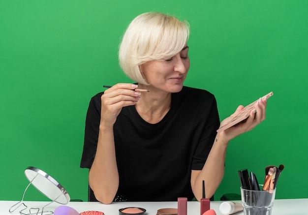 눈을 감고 웃고 있는 아름다운 소녀는 녹색 배경에 분리된 메이크업 브러시가 있는 아이섀도 팔레트를 들고 화장 도구를 들고 테이블에 앉아 있습니다.