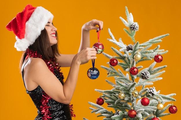 Улыбаясь с закрытыми глазами, молодая красивая девушка в новогодней шапке с гирляндой на шее стоит рядом с елкой и держит елочные шары на оранжевом фоне