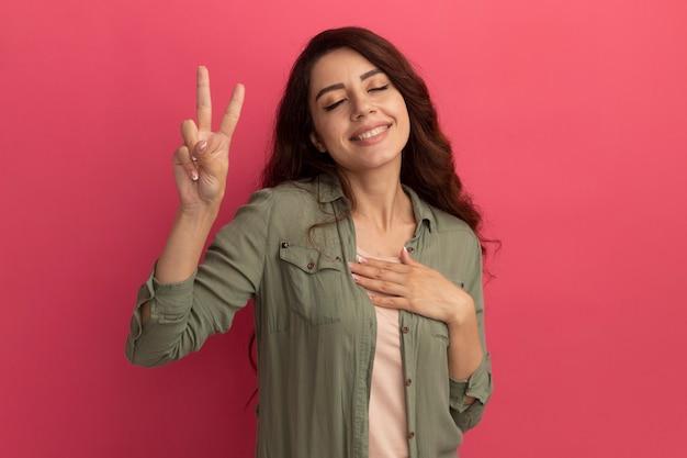 Улыбаясь с закрытыми глазами, молодая красивая девушка в оливково-зеленой футболке, демонстрирующая жест мира, изолирована на розовой стене