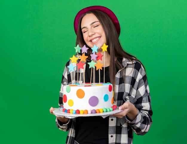 Smiling with closed eyes young beautiful girl wearing party hat holding cake