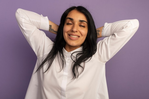 Smiling with closed eyes young beautiful girl wearing white t-shirt holding hands on behind head isolated on purple