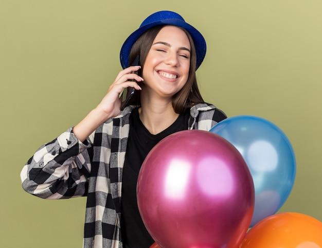 파란 모자를 쓰고 풍선 근처에 서 있는 아름다운 젊은 여성이 올리브 녹색 벽에 격리된 전화로 말하며 눈을 감고 웃고 있습니다.