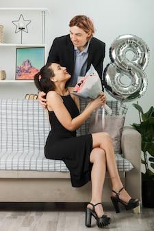 Улыбаясь с закрытыми глазами, молодая пара в счастливый женский день, парень, стоящий за диваном, девушка держит букет в гостиной