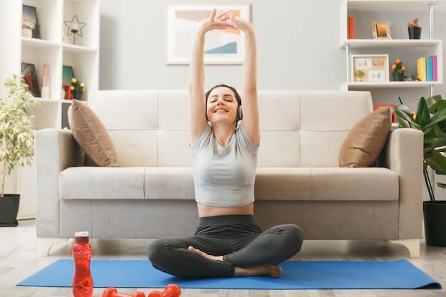 目を閉じて微笑むリビングルームのソファの前でヨガマットで運動するヘッドフォンを身に着けている若い女の子
