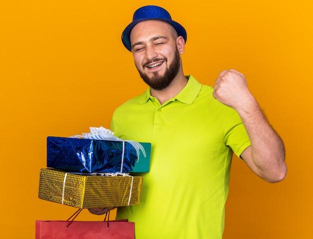 Улыбающийся с закрытыми глазами молодой человек в партийной шляпе, держащий подарочные коробки с сумкой, показывающий жест да, изолированный на оранжевой стене
