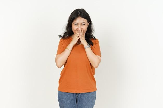 白で隔離オレンジ色のtシャツを着て美しいアジアの女性の口を覆うと笑顔