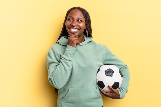 Smiling with a happy, confident expression with hand on chin, wondering and looking to the side. soccer concept