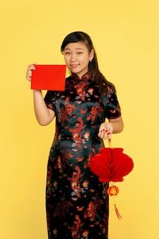 提灯と封筒で笑顔。ハッピーチャイニーズニューイヤー2020。黄色の背景にアジアの若い女の子の肖像画。伝統的な服を着た女性モデルは幸せそうに見えます。お祝い、感情。コピースペース。