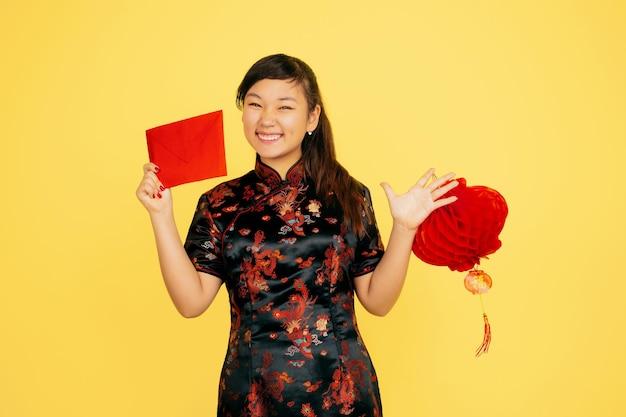 提灯と封筒で笑顔。ハッピーチャイニーズニューイヤー2020。黄色の背景にアジアの若い女の子の肖像画。伝統的な服を着た女性モデルは幸せそうに見えます。コピースペース。