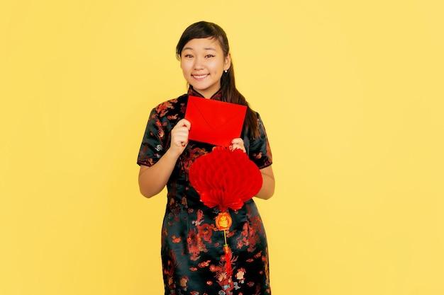 랜턴과 봉투와 함께 웃고. 행복 한 중국 새 해 2020. 노란색 배경에 아시아 젊은 여자의 초상화. 전통 옷을 입은 여성 모델이 행복해 보입니다. copyspace.