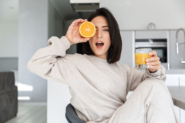 Smiling woman 30s drinking orange juice, while resting in bright modern room
