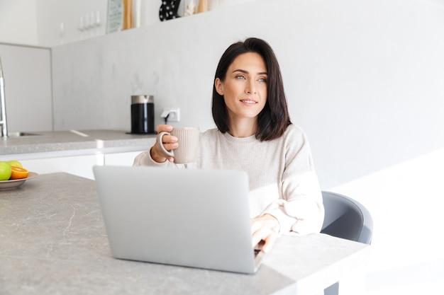 Улыбающаяся женщина 30 лет работает на ноутбуке, сидя на белой стене в светлой комнате
