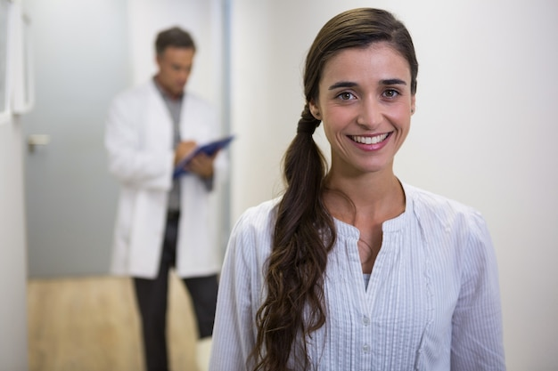 Smiling woman against dentist standing in lobby