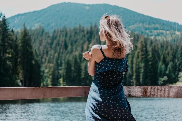 山の風景と湖に対して笑顔の女性。シネビル湖、ウクライナ、カルパティア山脈