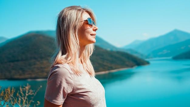 山の風景と湖に対して笑顔の女性。山とzhinvali貯水池湖の風景。メインのコーカサスの尾根。