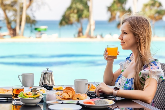 Smiling woman on american breakfast drinking orange juice next to poolside in resort. morning food near swimming pool in luxury hotel. summer holidays in tropical country, thailand. travel and relax