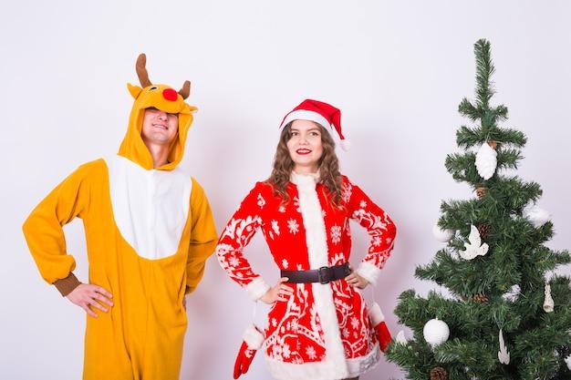 크리스마스 트리 근처 크리스마스 정장에 웃는 여자와 남자