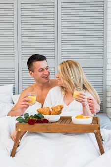 Smiling woman and man with glasses in bed near food on breakfast table