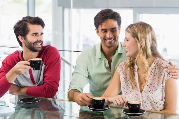笑顔の女性と一杯のコーヒーを持つ2人の男性