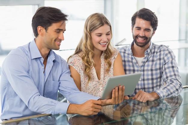 デジタルタブレットを使用して笑顔の女性と2人の男性
