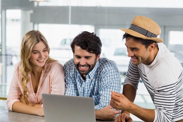 ラップトップを使用して笑顔の女性と2人の男性