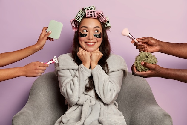Smiling woman applies eye patches and hair curlers, surrounded by many beauticians