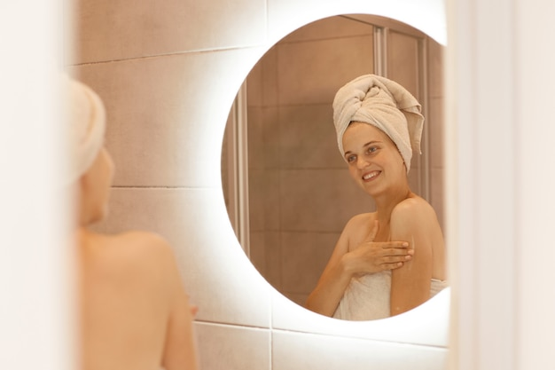 Smiling woman applying body lotion on arm and shoulders, looking at mirror reflection with happy expression, doing spa procedures at home, wrapped in white towel.