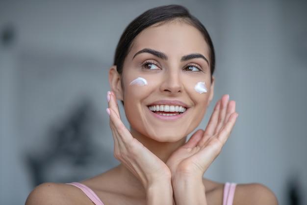 Улыбающаяся женщина, наносящая крем на щеки