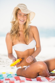 Smiling woman applying sunscreen