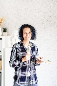Smiling woman artist in her studio holding art palette and paintbrushes
