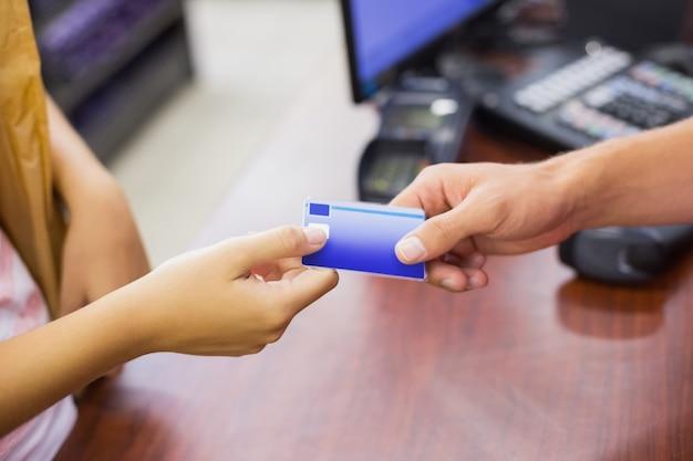 Улыбка женщины в кассе с кредитной картой