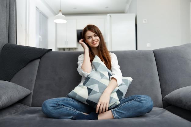 Улыбается женщина дома с подушкой в руках удобный диван в квартире.