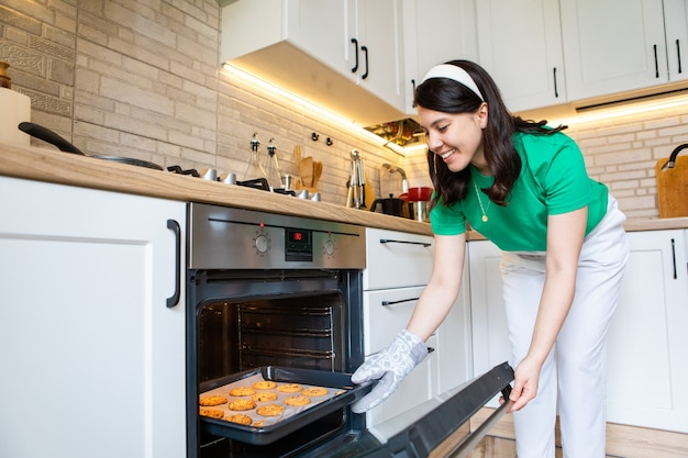 国内のキッチンコピースペースでクッキーを焼く笑顔の女性