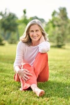 Улыбающаяся женщина босиком сидит на траве