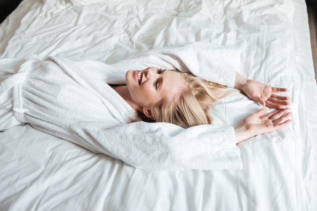 Smiling woman in bathrobe resting on bed