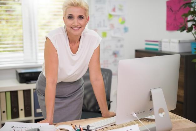 机の後ろに笑顔の女性 無料写真